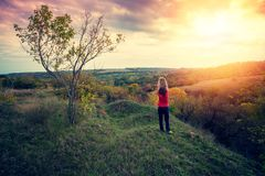 Young woman with hands up stands on the top of a hill stock photography