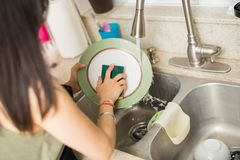 Woman hand washing dishes over the sink in the kitchen. Young woman hands washing dishes in the sink in the kitchen using sponge stock images