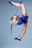 Young woman hanging in aerial ring on a blue background Royalty Free Stock Image
