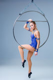 Young woman hanging in aerial ring on a blue background Royalty Free Stock Images