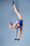 Young woman hanging in aerial ring on a blue background Stock Photography