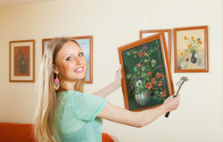 Young woman hanging the art picture Royalty Free Stock Photo