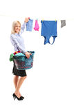 Young woman hanging clothes on clothes line. Full length portrait of a young smiling woman hanging clothes on clothes line using clothes peg  on white background Stock Images
