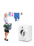 Young woman hanging clothes next to a ma Stock Images