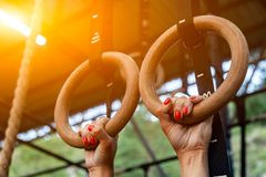 Young woman hanging on gym rings. Close-up Young woman hanging on gym rings, hands in magnesia against the backdrop of gym stock image