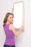 Young woman hanging mirror on wall. Royalty Free Stock Photos