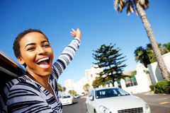 Young woman hanging outside car window with arms raised Stock Photo