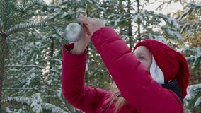 Young woman hanging silver ball on New Year tree branch in snowy forest. Happy girl teenager decorating Christmas tree stock video