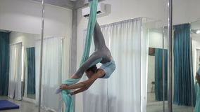 Young woman hanging upside down in hammock studio indoors. Female hangs inverted asana, with forces of gravity and zealously practices anti-gravity yoga. In stock video