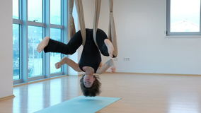 Young woman hanging upside down in hammock for yoga indoors. She slowly swings body with her legs wide apart and holds them with her fingers then she fully stock video footage