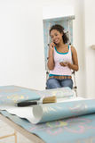 Young woman hanging wallpaper, resting on ladder with mug, using mobile phone, smiling royalty free stock photography