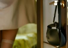 Young woman hangs a bra on the door handle. girl in stockings and towel in hotel room royalty free stock image