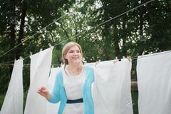 Young woman hangs white clean sheets in the garden. Domestic responsibilities. A woman smiles and catches soap bubbles.  Great royalty free stock photos