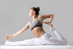 Young woman in Hanumanasana pose against grey studio background Royalty Free Stock Image