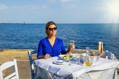 Young woman in a restaurant by the sea stock photos