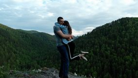 A young woman happily hugs her boyfriend standing on top of a mountain. stock video footage
