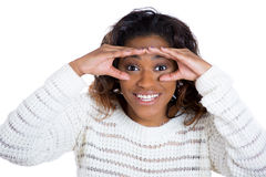 Young woman happily looking through her fingers like binoculars Royalty Free Stock Photography