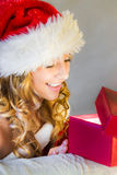 Young woman happily opens a gift Stock Photos
