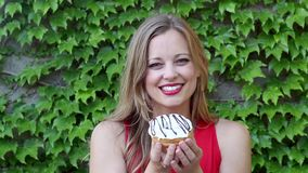 Young Woman Happily Showing Off White Donut with Chocolate Drizzle with Ivy Stock Photo