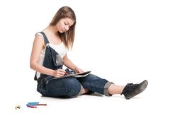 Young woman happily sitting  on the floor drawing. Young woman happily sitting on the floor drawing in her note pad.  On a white background Stock Photo