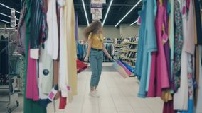 Young woman is happily spinning around in a clothing store. Happy shopping concept.