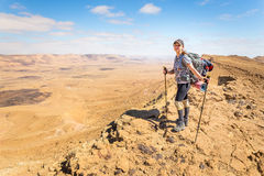 Young woman happy cheerful tourist backpacker standing  desert mountain edge Stock Photos
