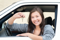 Young woman happy about her new drivers license. Young woman sitting in car and showing key. She is happy about her new drivers license or new car stock photography