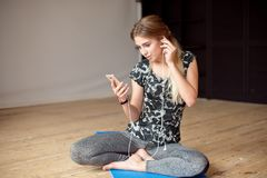 Young woman happy singing her favorite song while listening music sitting on the floor. Young woman happy singing her favorite song while listening music royalty free stock photo