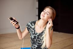 Young woman happy singing her favorite song while listening music sitting on the floor. Young woman happy singing her favorite song while listening music royalty free stock images