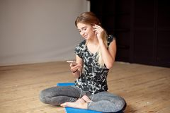 Young woman happy singing her favorite song while listening music sitting on the floor. Young woman happy singing her favorite song while listening music stock images