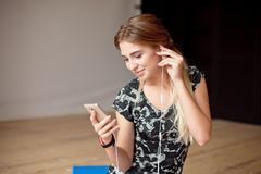 Young woman happy singing her favorite song while listening music sitting on the floor. Young woman happy singing her favorite song while listening music stock image