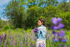 Young woman, happy, standing among the field of violet lupines, smiling, purple flowers. Blue sky on the background. Summer, with. Young woman, brunette, happy Stock Images
