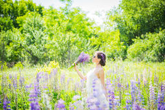 Young woman, happy, standing among the field of violet lupines, smiling, purple flowers. Blue sky on the background. Summer, with. Young woman, happy, standing Royalty Free Stock Photos