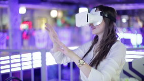 Young woman is happy in virtual reality glasses. VR. Shopping and entertainment center in the background