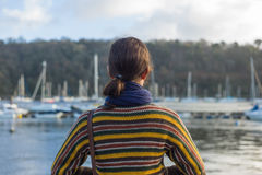 Young woman in harbor looking at boats Stock Image