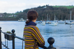 Young woman in harbor looking at boats Stock Photos