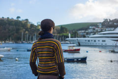 Young woman in harbor looking at boats Royalty Free Stock Photography