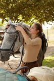 Young woman harnessing horse royalty free stock photo