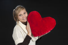 Young woman with hart shaped pillow on black Royalty Free Stock Photos