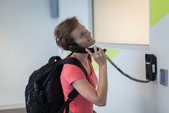The young woman has been complaining to the airport by telephone. On the wall Stock Image