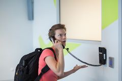 The young woman has been complaining to the airport by telephone. On the wall Royalty Free Stock Photo