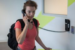 The young woman has been complaining to the airport by telephone. On the wall Stock Photography
