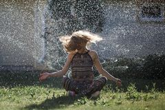 Young woman has fun with a spray of water stock photo