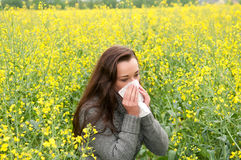 Young woman  has hay fever. Young woman in rape field  has hay fever Royalty Free Stock Photos