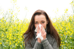 Young woman has hay fever. Young woman in rape field  has hay fever Royalty Free Stock Photography