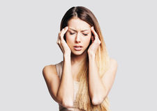 Young woman has headache. Young beautiful woman has headache over gray background Stock Photo