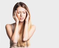 Young woman has headache, on a gray background. Young beautiful woman has headache on a gray background Royalty Free Stock Image