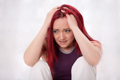 Young woman has a headache. Young red haired woman suffers desperately of a headache Royalty Free Stock Photos