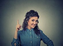 Young woman has idea, pointing with finger up Royalty Free Stock Photos