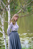 The young woman has leaned against the blossoming birch of useful Himalaya Betula utilis D.Don. On the bank of a pond royalty free stock photo